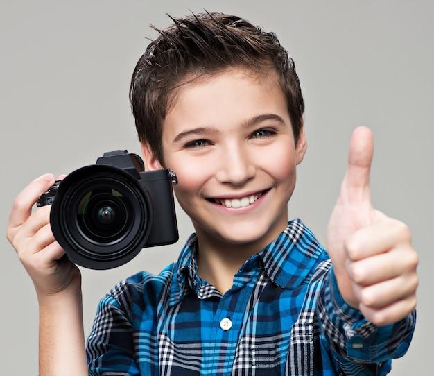 写真を撮るカメラを持つ少年。親指を上に表示しているデジタル一眼レフカメラで幸せな楽しい男の子