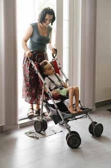 特別な椅子に脳性麻痺の少年が母親のアクセスで外に出る