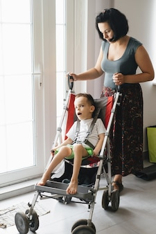 Boy with cerebral palsy in special chair going outside with mother access