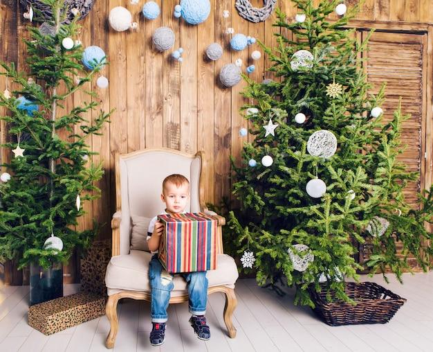 クリスマスツリーの近くのクリスマスプレゼントを持つ少年