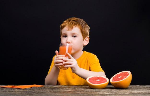 柑橘系の果物を持つ少年