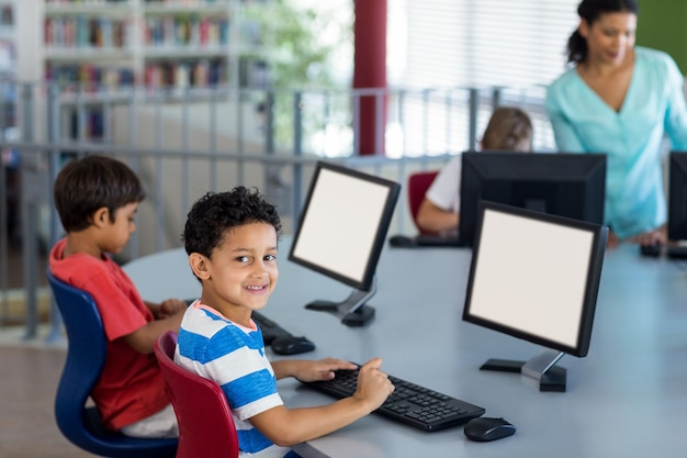 Boy with classmates and teacher during computer class