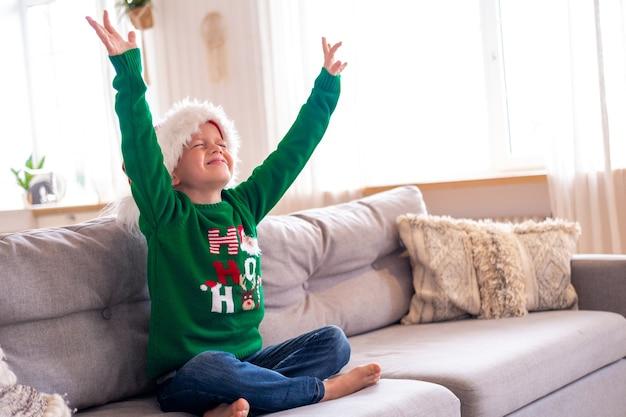 サンタの帽子とクリスマスの衣装で目を閉じて家に座っている少年は手を上げます