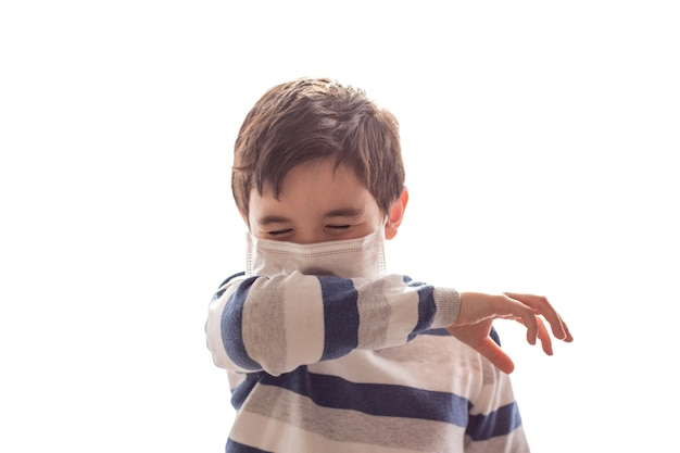 A boy with closed eyes sneezes or coughs into his elbow on white background.