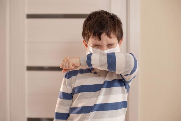 目を閉じている男の子はくしゃみをするか、彼の肘に咳をします。