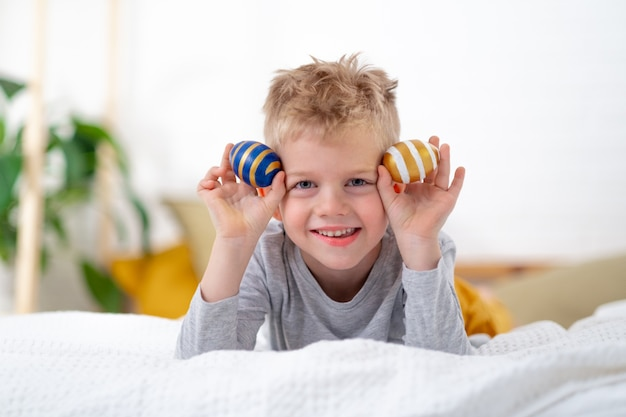 Boy with colored eggs lying on bed at home