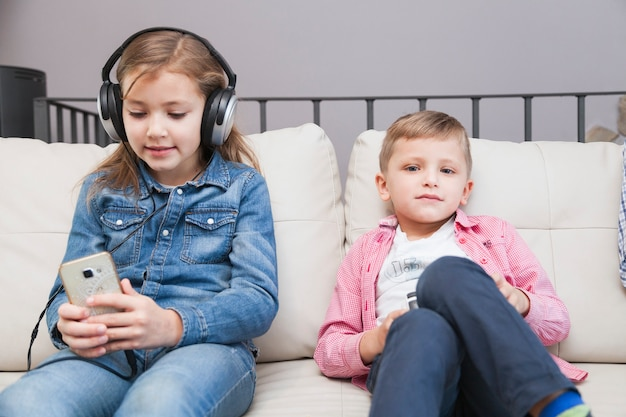 Boy with controller and girl with smartphone