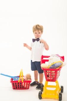 Мальчик с кредитной картой, делая покупки со скидкой, счастливый маленький мальчик с тележкой для покупок и корзиной