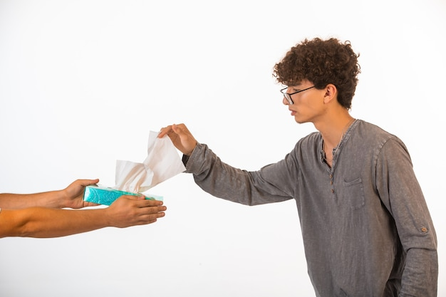 Boy with curly hairs and in optique glasses taking a tissue from the box.