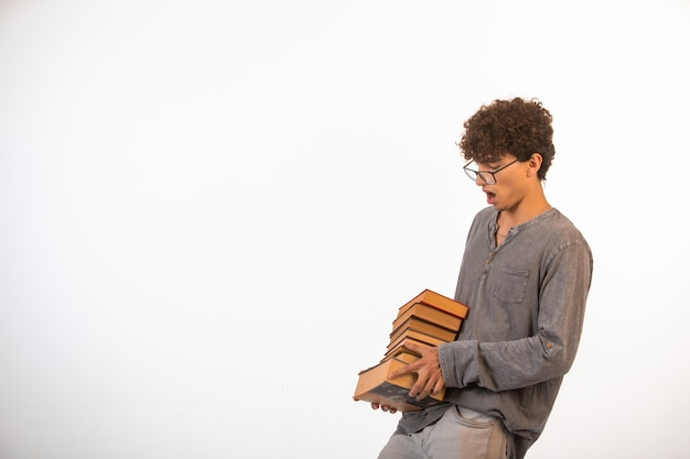 Boy with curly hairs wearing optique glasses barely holds a stock of books.