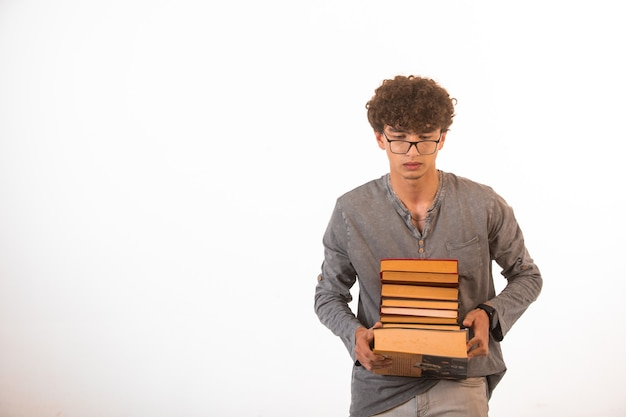 Boy with curly hairs wearing optique glasses carrying a pile of books.