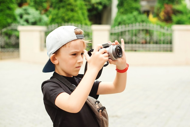 Boy with a digital camera taking pictures. future profession. summer holidays, memories and impressions.
