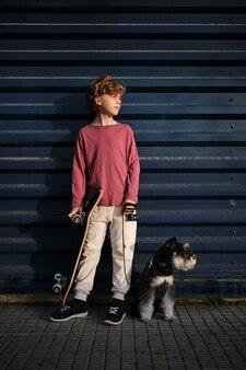 通りに犬とスケートボードを持つ少年