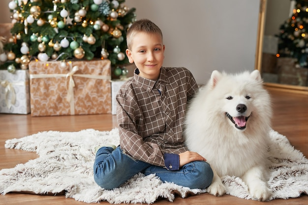 Boy with dog near christmas tree on christmas