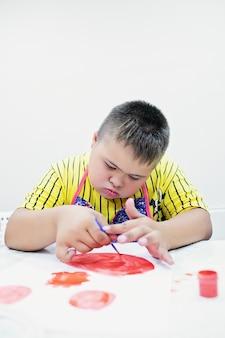 Мальчик с синдромом дауна рисует за столом на белом фоне. фото высокого качества