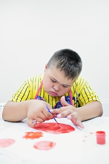 Boy with down syndrome draw at a table on a white background. high quality photo