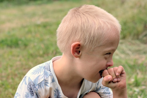Boy with down syndrome poses for a portrait outdoors