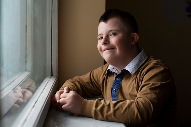Boy with down syndrome posing by window