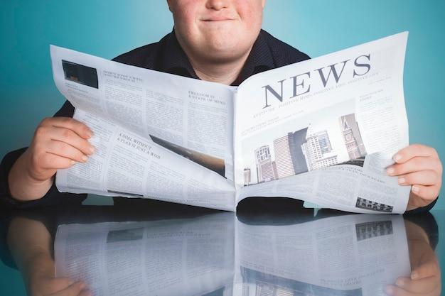 코로나 바이러스 전염병 동안 신문을 읽는 다운 증후군을 가진 소년