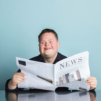 Boy with down syndrome reading a newspaper during the coronavirus pandemic