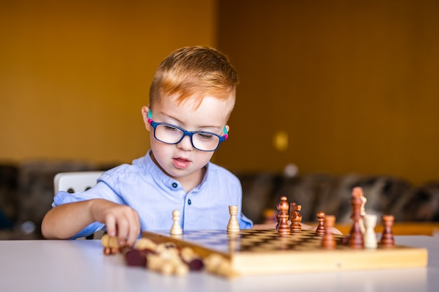 Boy with down syndrome with big glasses playing chess.