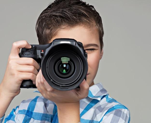 デジタル一眼レフカメラ撮影の少年。写真を撮るカメラを持つ10代の少年。