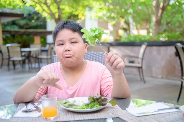 Boy with expression of disgust against vegetables