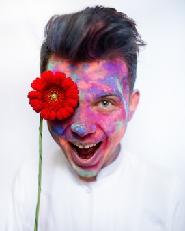 Boy with face covered with paints holds red flower before his eye