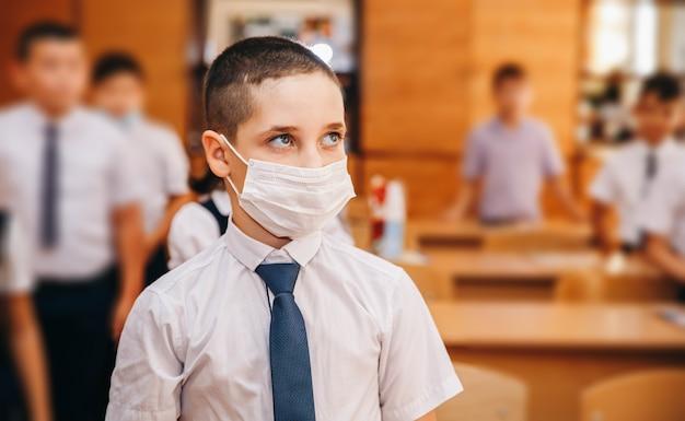 Мальчик в маске вернулся в школу после карантина и изоляции от covid-19