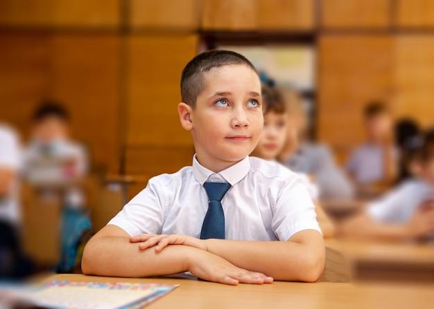 Covid-19検疫と封鎖の後に学校に戻ってフェイスマスクを持つ少年