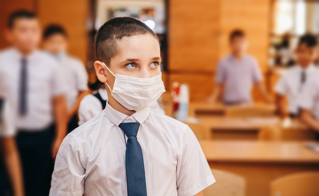 Boy with face mask back at school after covid-19 quarantine and lockdown