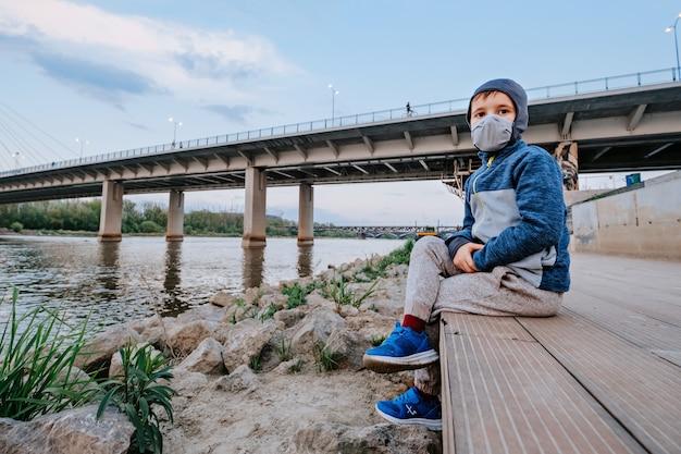 Boy with face mask at the lake coast