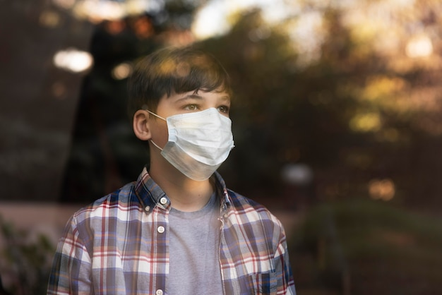 Boy with face mask on looking outdoors through the windows