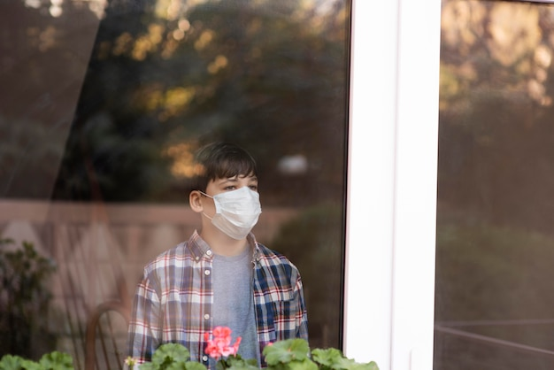 Boy with face mask on looking outdoors