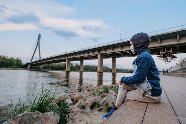 Boy with face mask looking at the river