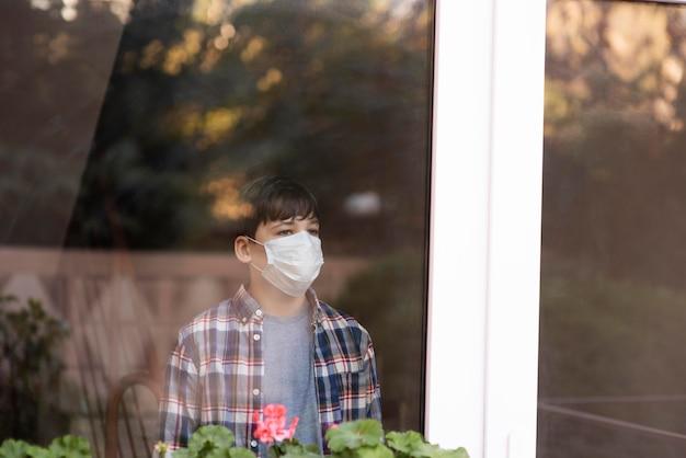 屋外を見てフェイスマスクを持つ少年