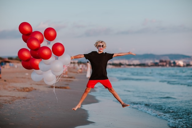 夏のショーツとシャツを着たピエロのような顔の絵を描いた少年は、砂浜で風船の束を持ってポーズをとっています。スペースをコピーします。