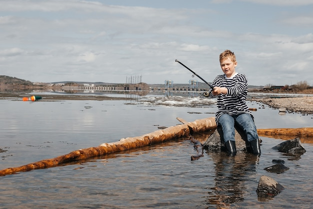 A boy with a fishing rod is fishing, sitting on the bank of the river. a handsome boy in a striped vest sits with a fishing rod in his hands Premium Photo