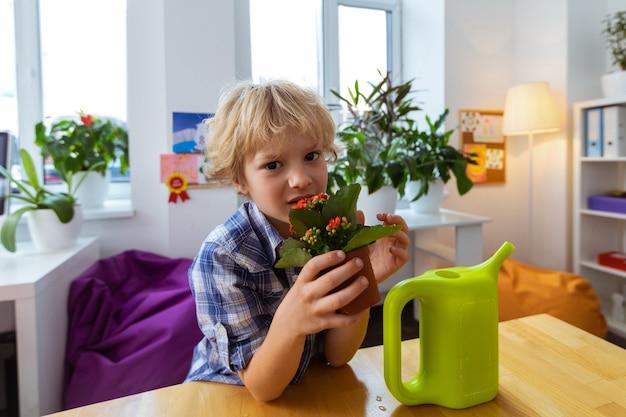 花を持つ少年。赤い花を保持しているじょうろとテーブルの近くに立っているかわいいブロンドの髪の少年