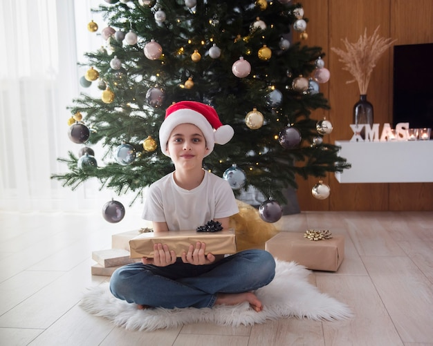 Boy with gifts plays near the christmas tree. living room interior with christmas tree and decorations. new year. gift giving.