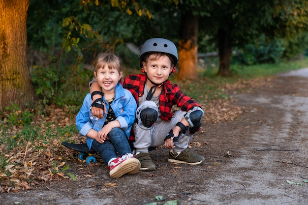 Boy with a girl sitting near the road with a skateboard