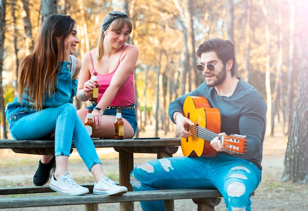 Boy with girls plays guitar and sings outdoors, party
