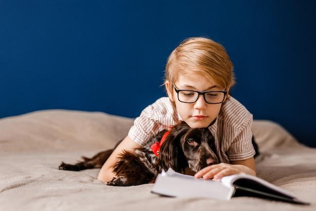 Мальчик в очках и со своей собакой лежит на кровати и читает большую книгу.