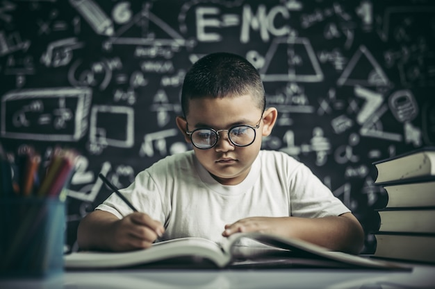 A boy with glasses man writing in the classroom