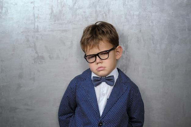 恨みと泣きの感情を持つ灰色の壁に眼鏡をかけた少年