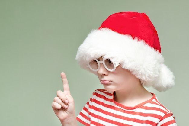 Boy with glasses and a santa hat is threatening with his finger