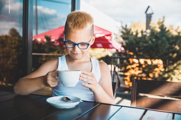 眼鏡をかけた少年がカフェに座ってコーヒーを飲む