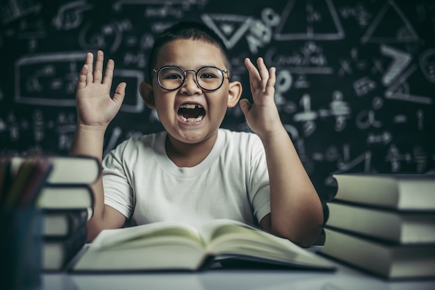 A boy with glasses sitting in the classroom reading