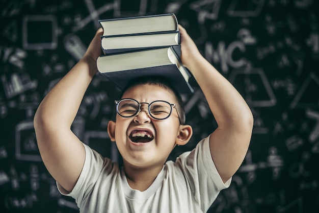 A boy with glasses studied and put a book on his head in the classroom.