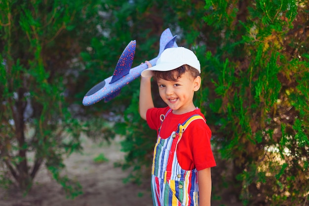 Boy with glider in his hands a child plays with a plane on the street in the park playing outdoors b...